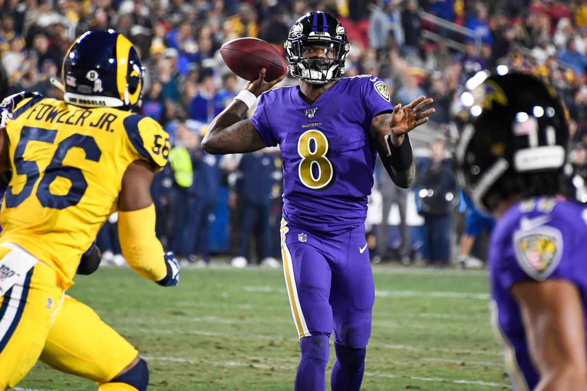 Baltimore Ravens quarterback Lamar Jackson throws a touchdown pass to wide receiver Marquise Brown in the first quarter at Los Angeles Memorial Coliseum.