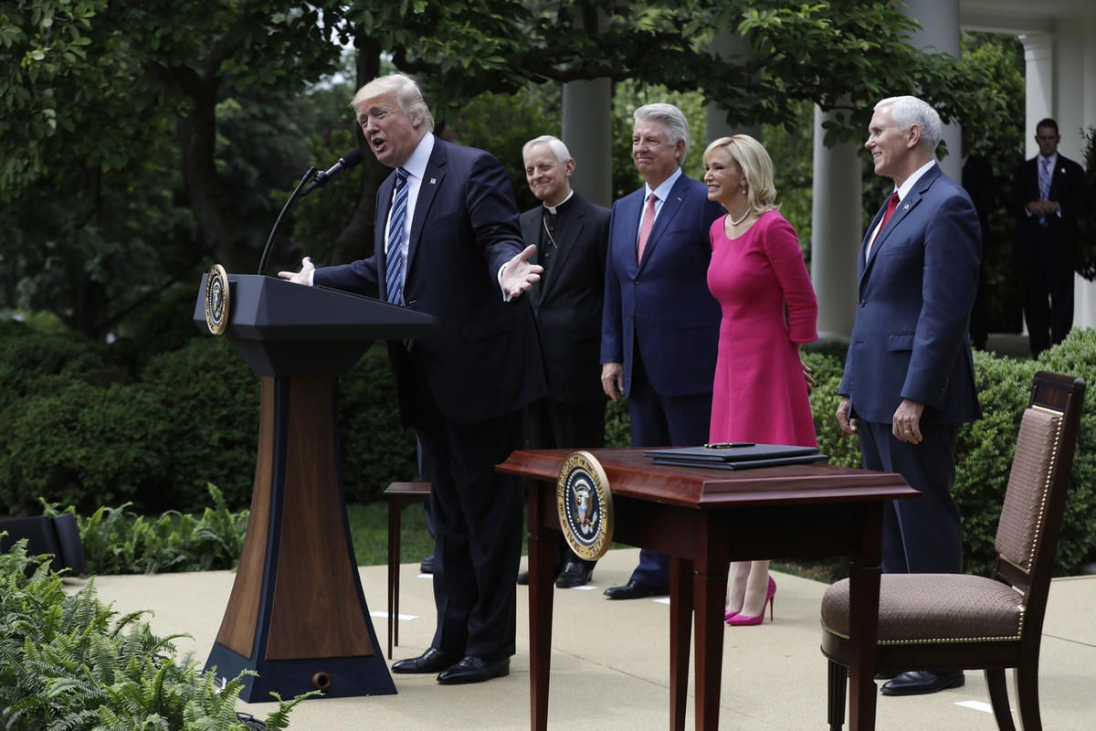 President Donald Trump speaks in the Rose Garden of the White House in Washington, Thursday, May 4, 2017, before signing an executive order aimed at easing an IRS rule limiting political activity for churches. From second from left are, Cardinal Donald Wu
