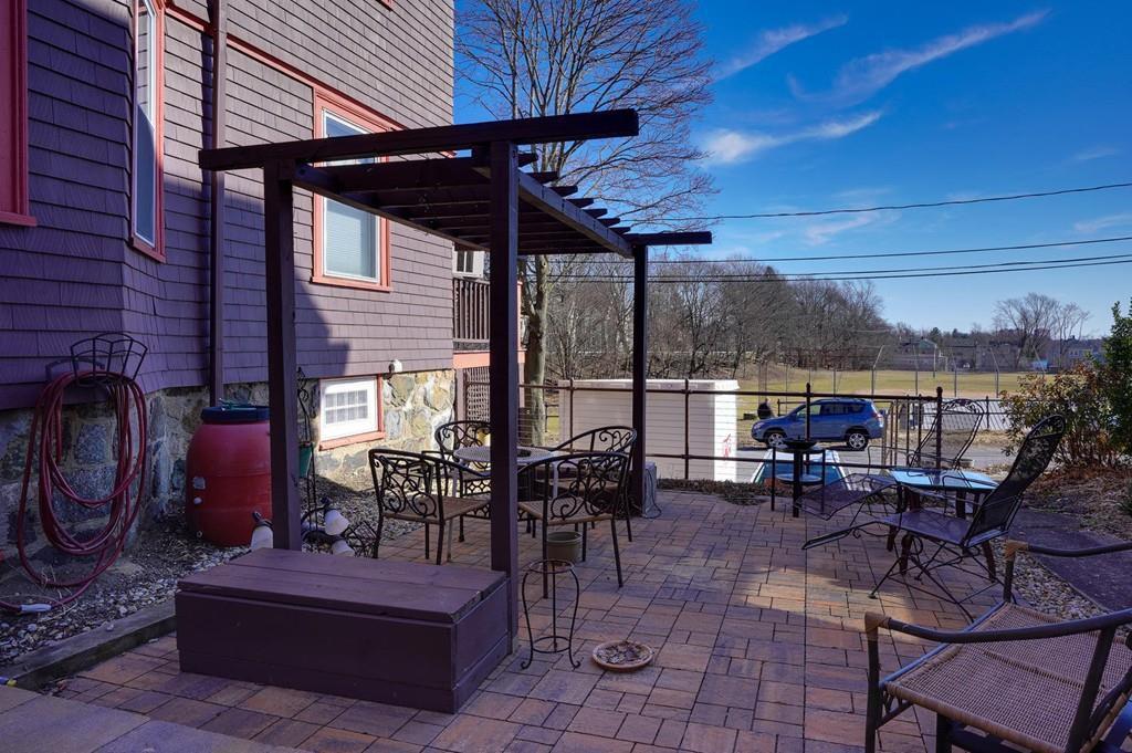 A brick patio next to a house, with a trellis.