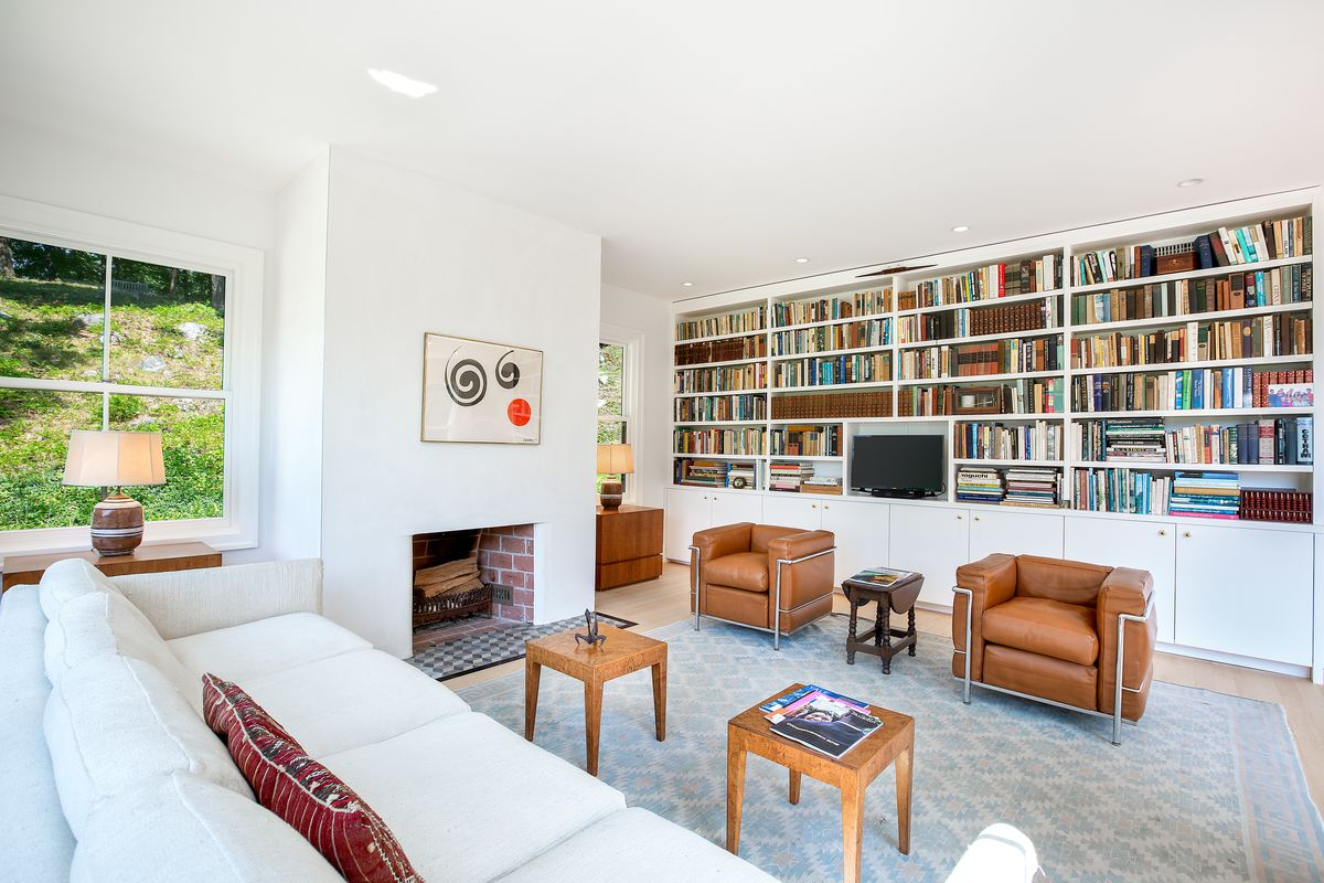 An all-white living room has bookshelves on one wall, a fireplace in the center, and a white couch with two leather arm chairs.