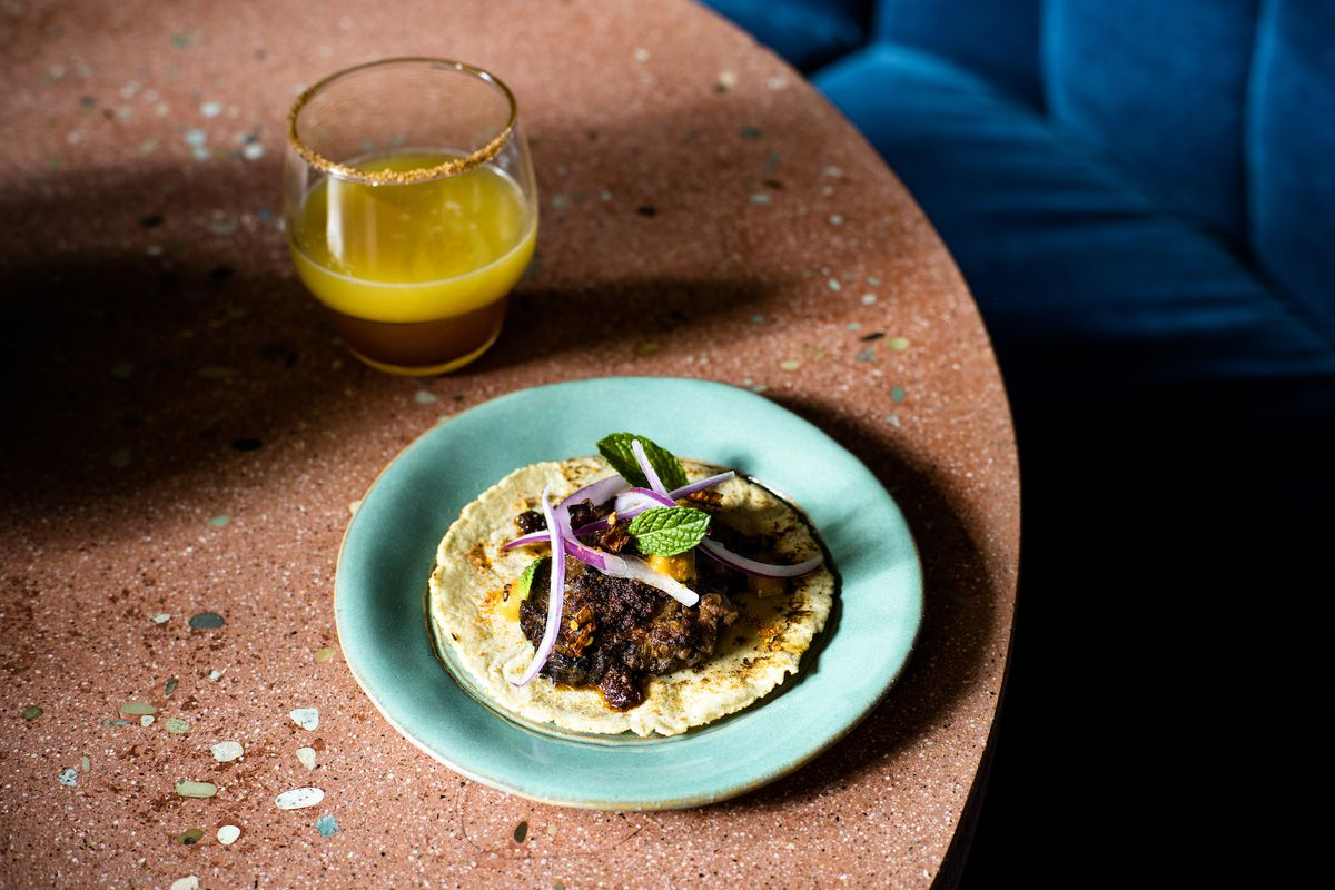 A lamb taco on a corn tortilla with a pink table and cocktail in background.