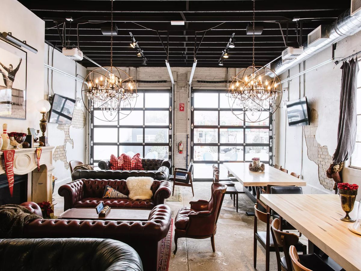 A white room filled with leather couches, tables, and two televisions.