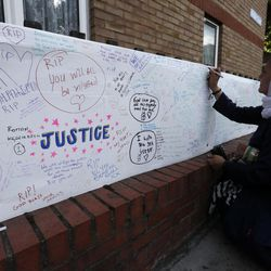 A woman signs a message board near Grenfell Tower in London, Saturday, June 17, 2017.  Police Commander Stuart Cundy said Saturday it will take weeks or longer to recover and identify all the dead in the public housing block that was devastated by a fire early Wednesday.