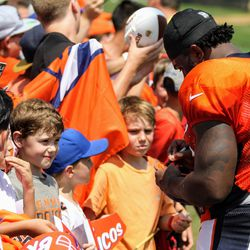 Running back for the Broncos De'Angelo Henderson Sr. signs autographs for fans after practice.