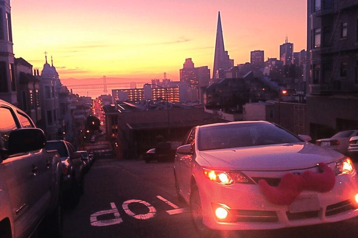 A car with a pink Lyft mustache driving through San Francisco at Sunset with the Transamerica Pyramid in the background.