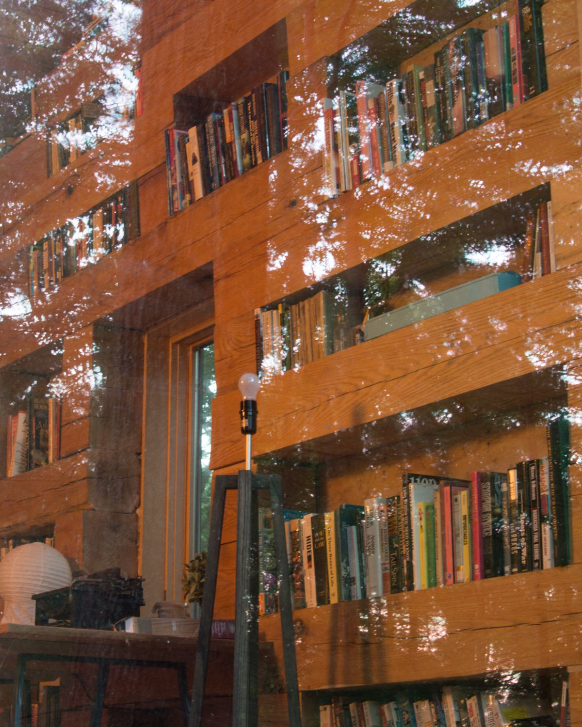 Looking through a big picture window, you can see bookshelves crafted with large, square beams (they are roughly 8 x 8) made from light-colored oak wood.