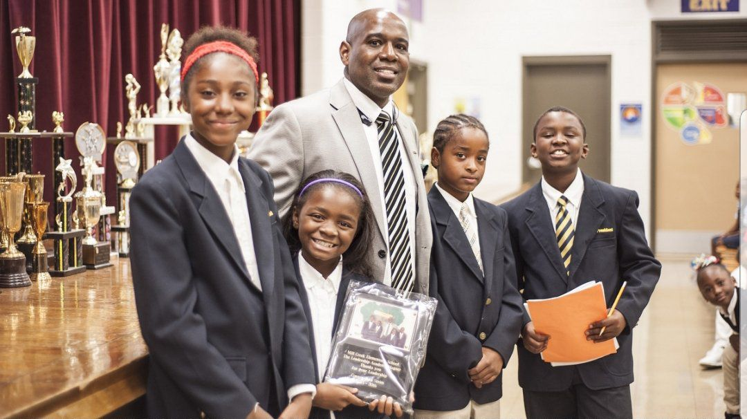 Chief Equity Officer John Marshall with students at Mill Creek Elementary's student Leadership Academy convocation.