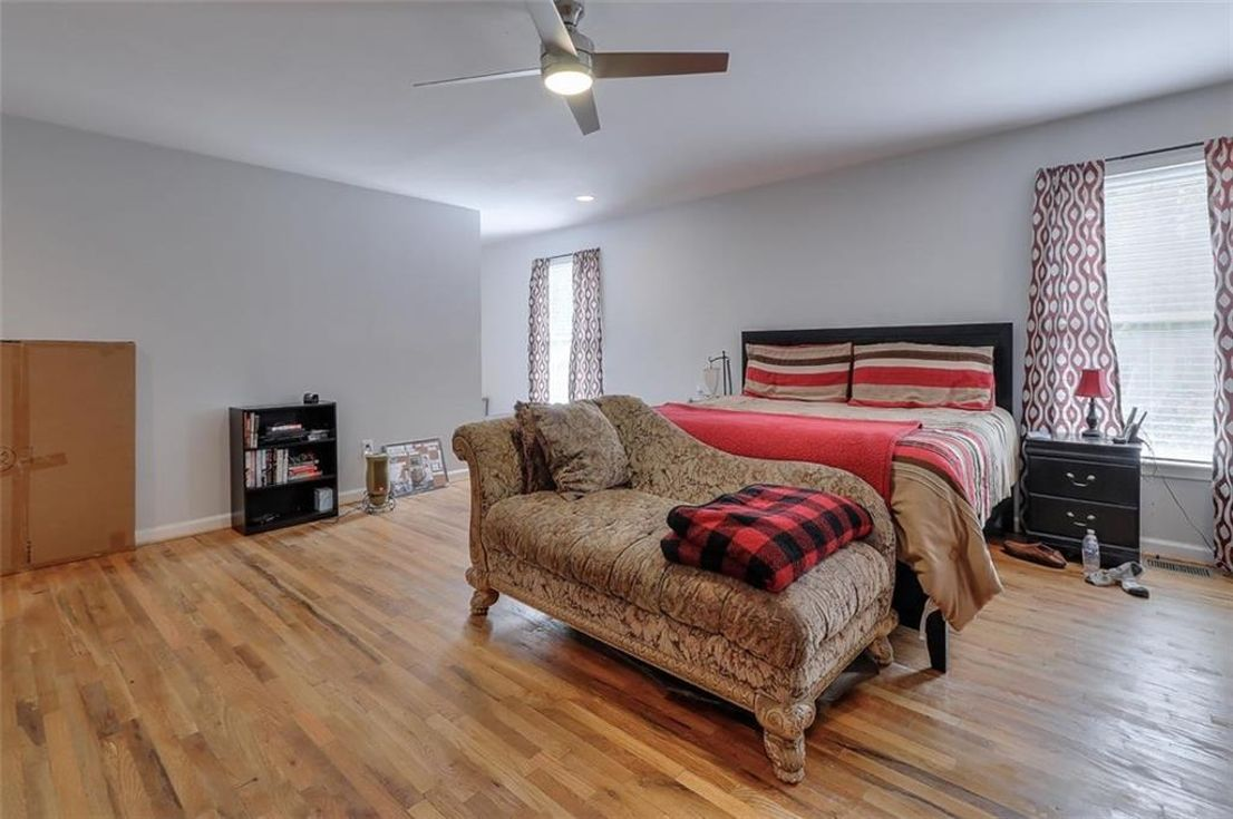 A huge bedroom with wooden floors.