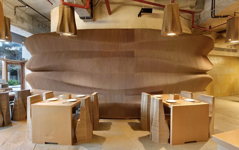 The inside of a cafe where the tables, chairs, and walls are all made out of corrugated cardboard.