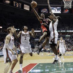 Toronto Raptors' Ben Uzoh (18) goes up for a shot against Milwaukee Bucks' Ekpe Udoh during the first half of an NBA basketball game Monday, April 23, 2012, in Milwaukee.