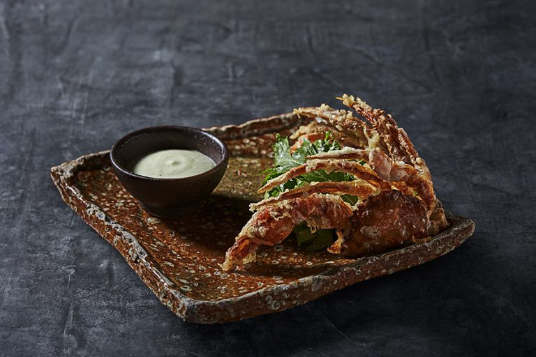 Soft-shell crab on a black plate