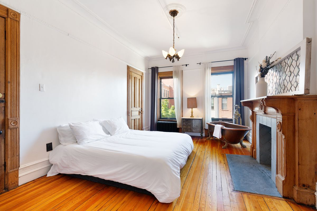 A large room with a bed, tow windows, wood fireplace, and copper tub in the corner.