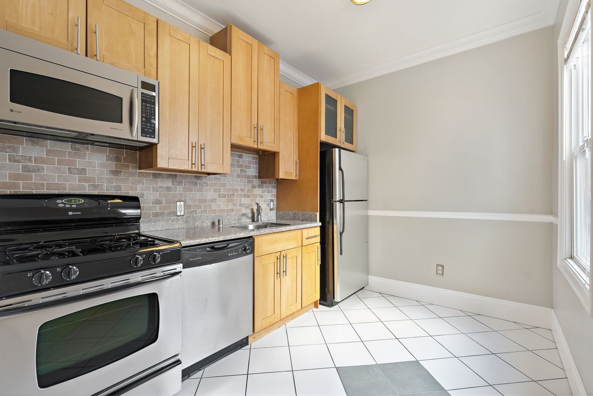 A kitchen with faux brick wall decor and two windows.
