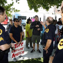 Salt Lake City police officers talk with a coalition of activists as they protest outside the Grand America Hotel. This is during the Mitt Romney visit to Salt Lake City, Tuesday, Sept. 18, 2012.