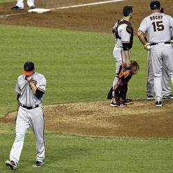 San Francisco Giants' Ryan Vogelsong, left, leaves the game after being pulled by manager Bruce Bochy (15) as Bochy talks with others, including catcher Buster Posey, in the fourth inning of a baseball game against the Arizona Diamondbacks, Sunday, Sept. 16, 2012, in Phoenix.