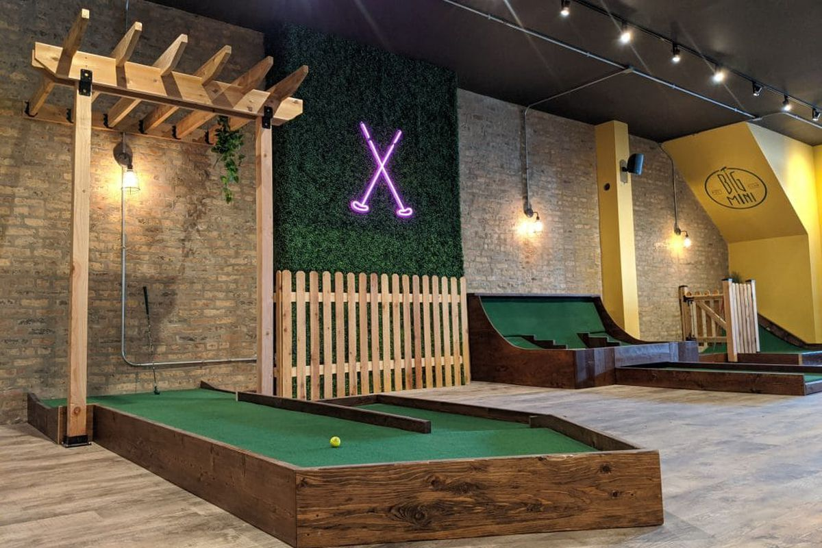 A large indoor mini-golf course with green astroturf and a large wooden pergola.
