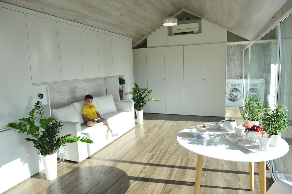 A child sits in an open living room with white cabinets, light wood floors, and white furniture.