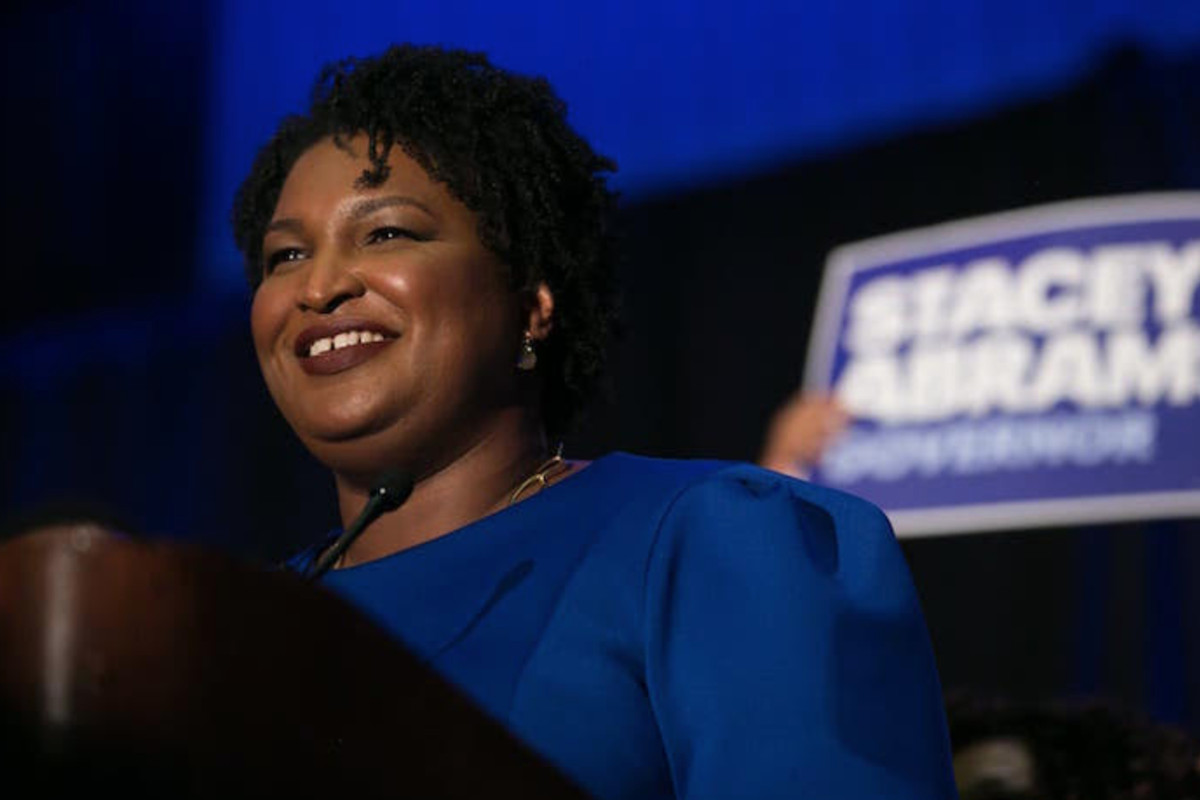 Stacey Abrams stands on a campaign stage.