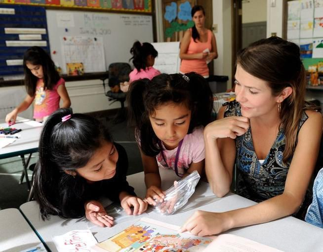 A teacher sits at a table with two girls. They look at a paper on the table.