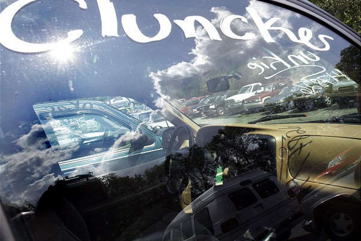 Vehicles traded in for the government's Cash for Clunkers program are seen through and reflected in a car window at a lot owned by Ira Toyota  in Danvers, Mass. Monday.