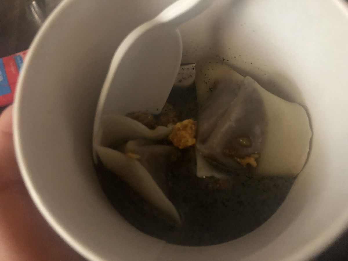 Two dumplings in a dark sauce inside a cup with a white plastic spoon