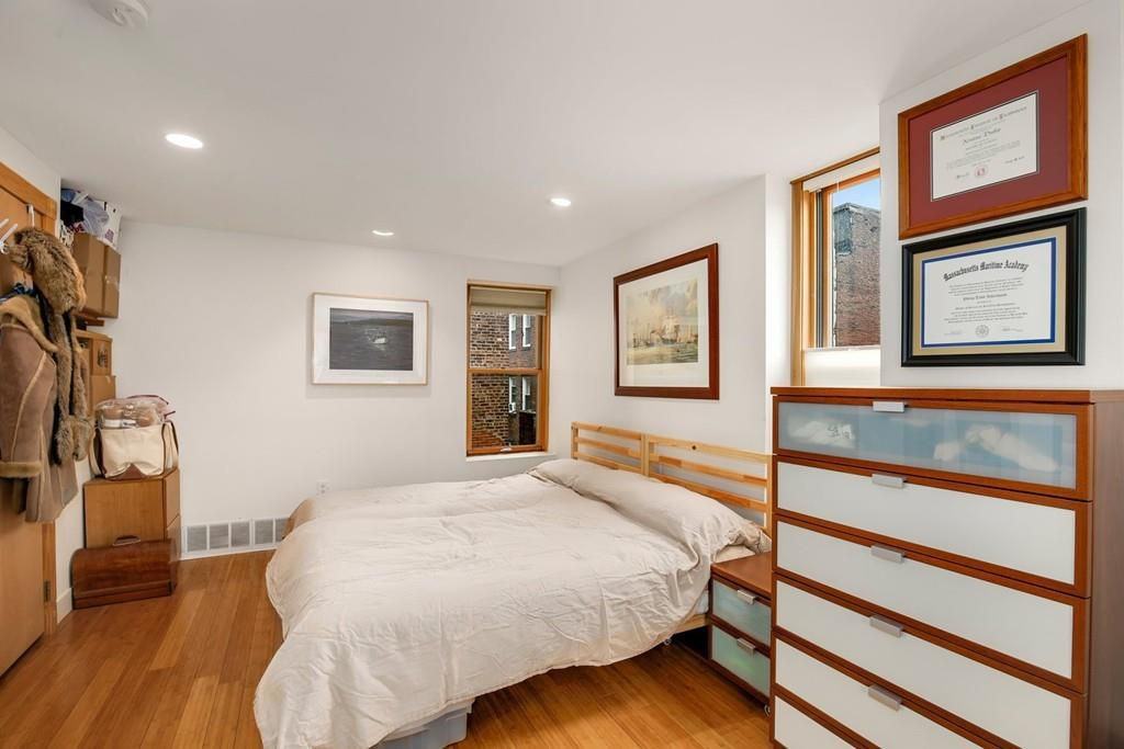 A bedroom with a bed and a tall dresser.