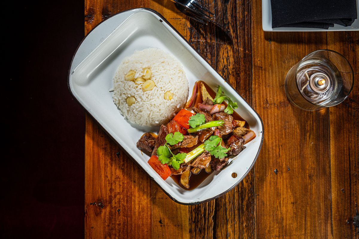 Lomo saltado, served in imported white metal tins, features juicy chunks of ribeye, red onion, scallions, tomato, and soy sauce atop a bed of fries and a dome of rice
