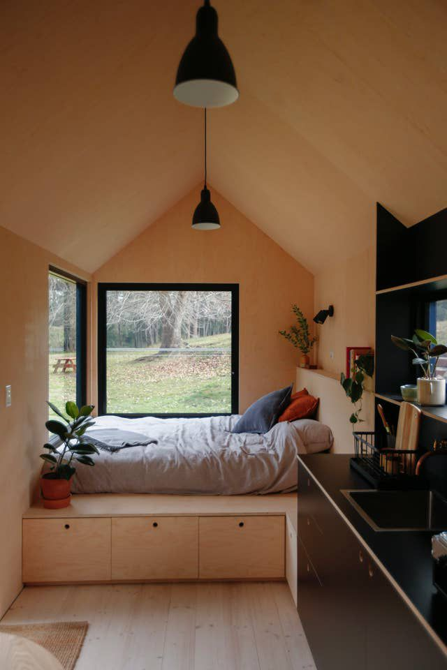 Interior view of a tiny house featuring pale wood walls, ceilings, floors, and built-in platform bed. There are black accents throughout including pendant lamps, rims on two picture windows, and the kitchenette.