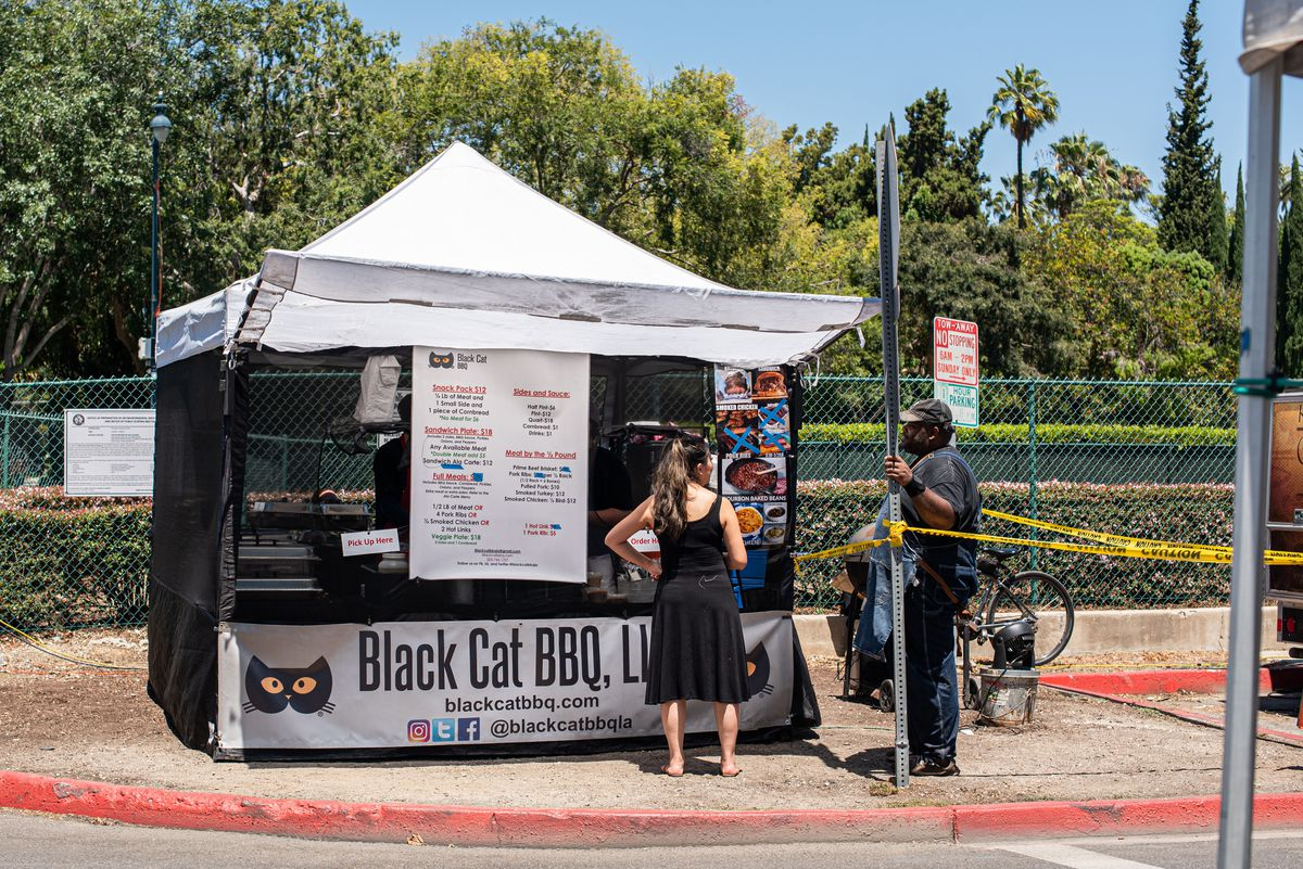 Two people discuss barbecue in front of a tent stand at a farmers market.