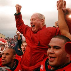 Utah head coach Ron McBride is hoisted to the players shoulders as the team celebrates after Utah beat BYU 13-6 at Rice-Eccles Stadium Saturday, November 23, 2002.