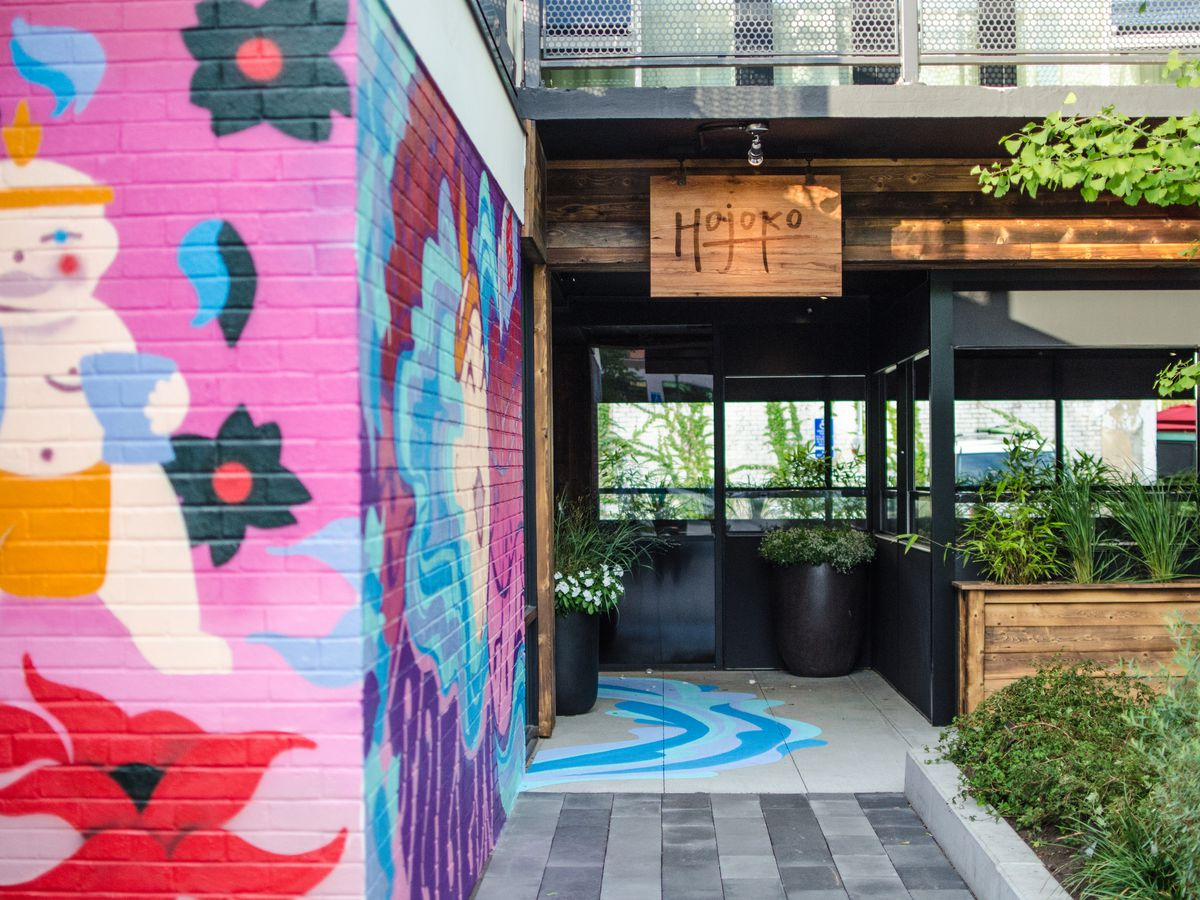 """A colorful Japanese-inspired mural leads to the door of a restaurant with wooden signage reading """"Hojoko."""" There's some greenery around the exterior."""