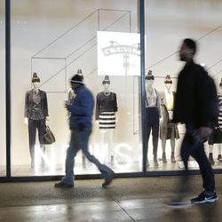 Pedestrians pass an H&M storefront window advertising discounts up to 75%, Tuesday, Jan. 14, 2014 in New York.