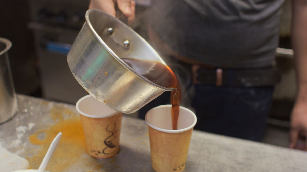 Chai being poured into a paper cup from a pot.