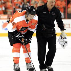 Philadelphia Flyers Brayden Scheen is lead to the bench by a trainer after being cross-checked to the ice then punched to the back of the head from Pittsburgh Penguins' Aaron Asham who received a 10-minute game misconduct and a match penalty during the first period of Game 3 in a first-round NHL Stanley Cup playoffs hockey series, Sunday, April 15, 2012, in Philadelphia. The Flyers' 8-4 win puts them ahead 3-0 in the series. (AP Photo/Tom Mihalek)