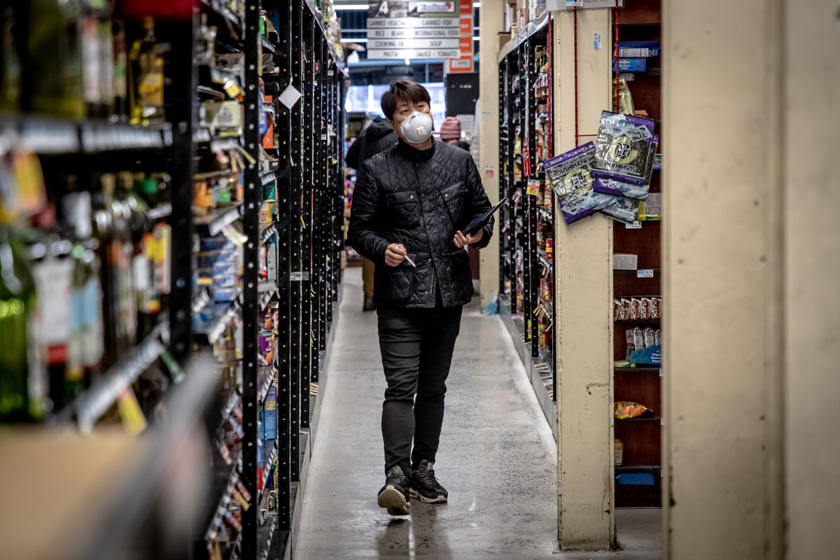 A man wearing a mask checks inventory in a supermarket