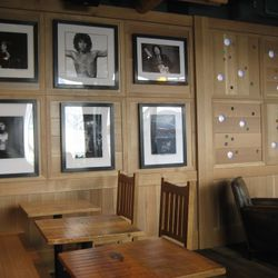 Rock and roll portraits from owner Ken Zanzel's personal collection adorn the walls. On the right, multi-colored back-lit European glass lenses create a glow.