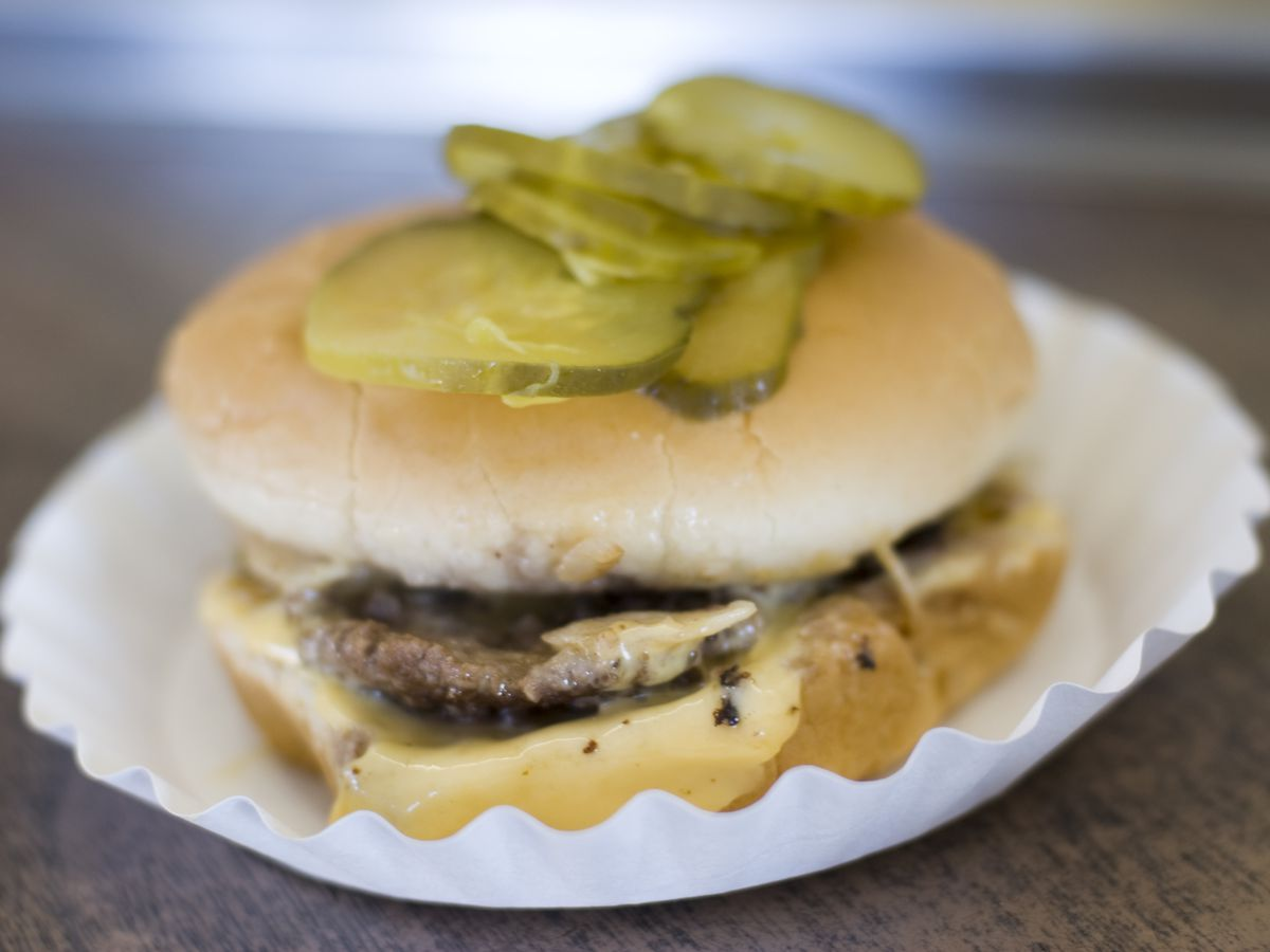 A thin cheeseburger sits on top of a cupcake wrapper, with a stack of pickles on its bun