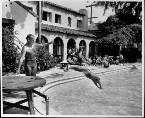 In the foreground is a swimming pool. A man is gesturing towards the pool. Another man is diving into the pool. In the background is a large mansion with archways. There are trees surrounding the area.