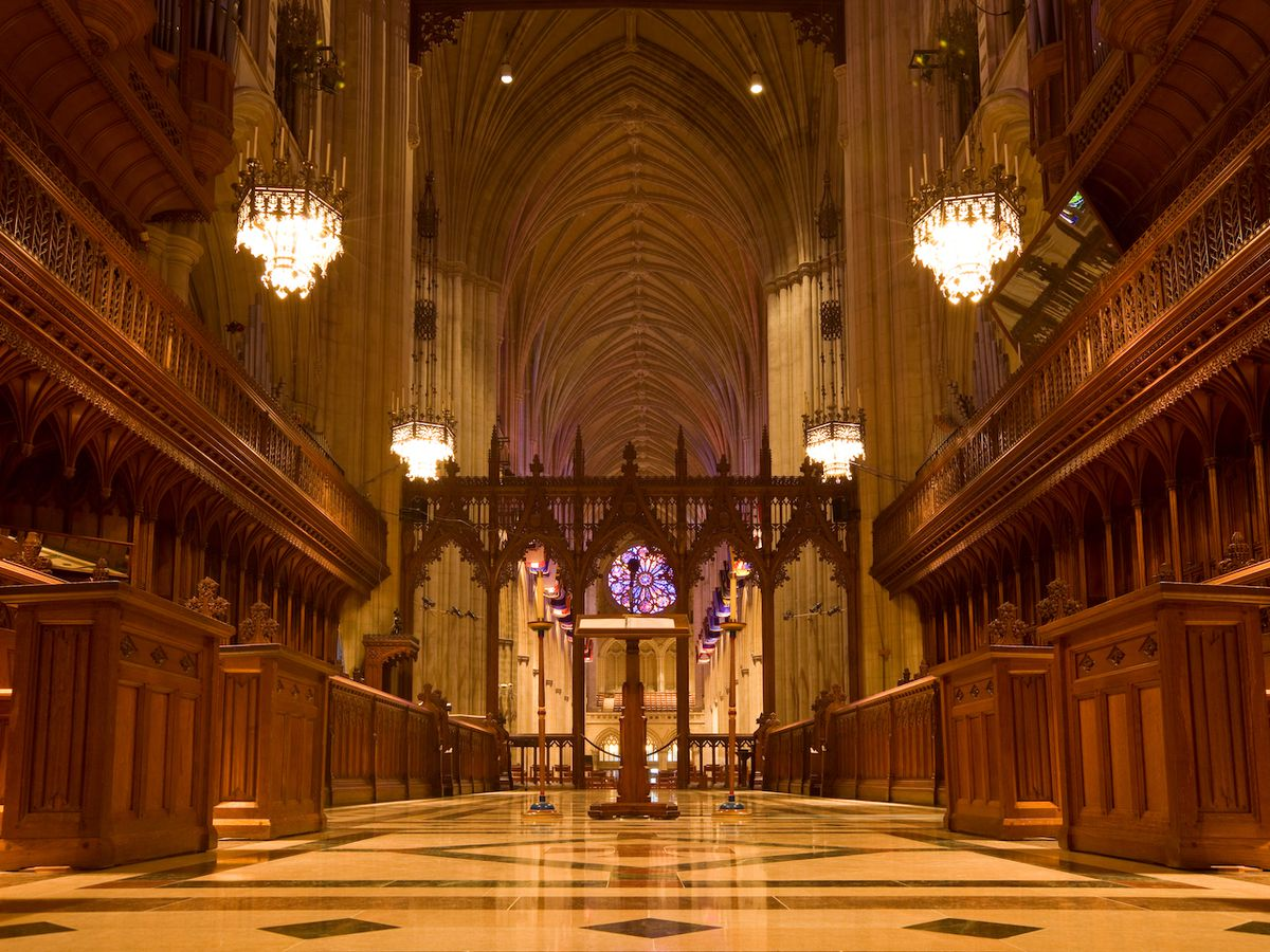 The inside of a cathedral. There are wooden seats for religious figures on either side of a central aisle.