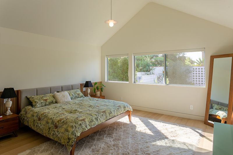 Bedroom with pitched roofs, a small pendant light, and wooden headboard.