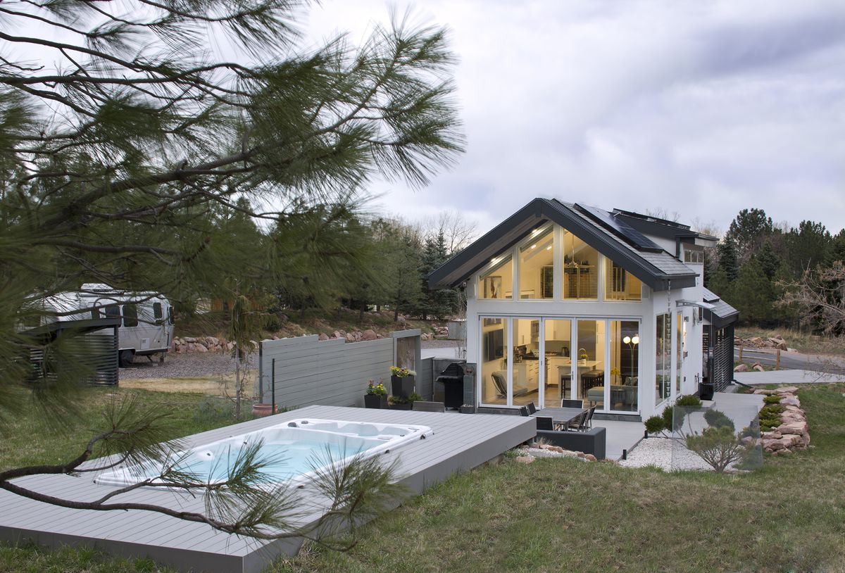 A lap pool is outside the house, it's surrounded by a deck.