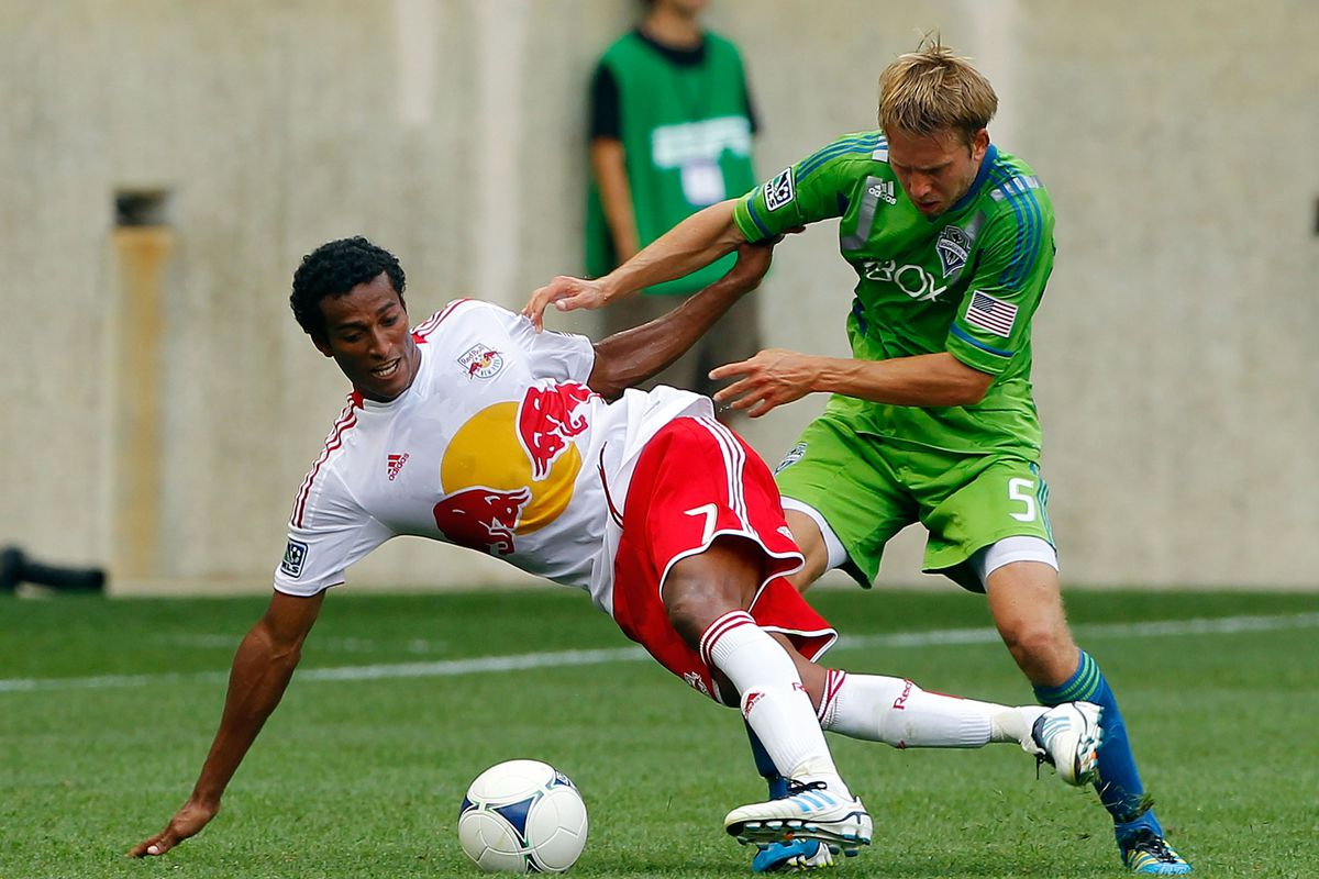HARRISON, NJ - JULY 15:  Roy Miller #7 of the New York Red Bulls is knocked from the ball against Adam Johansson #5 of the Seattle Sounders at Red Bull Arena on July 15, 2012 in Harrison, New Jersey.  (Photo by Jim McIsaac/Getty Images)
