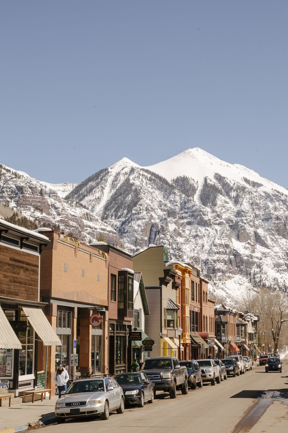 The town of Telluride, some shops and restaurants in a number of low buildings, with the mountain behind.