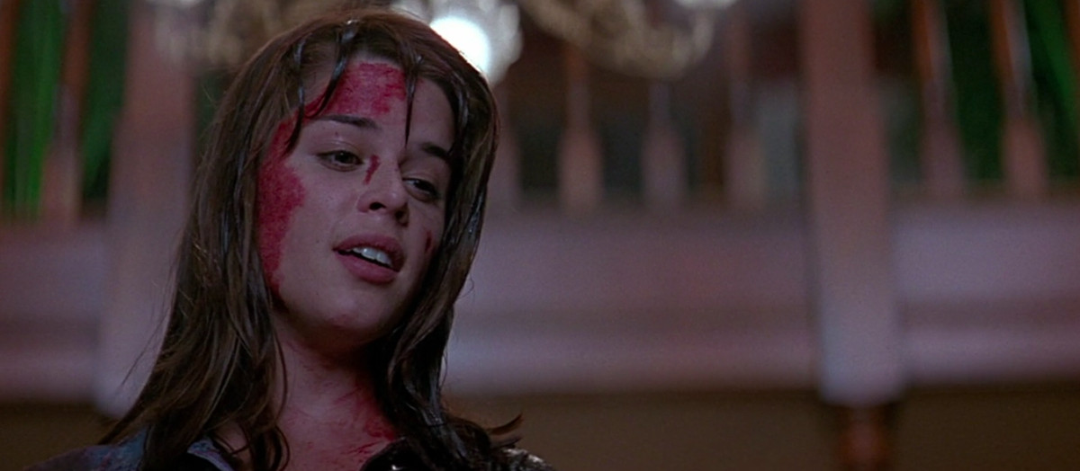 sidney (neve campbell) takes a look at the dead killer one last night, blood splattered across her face