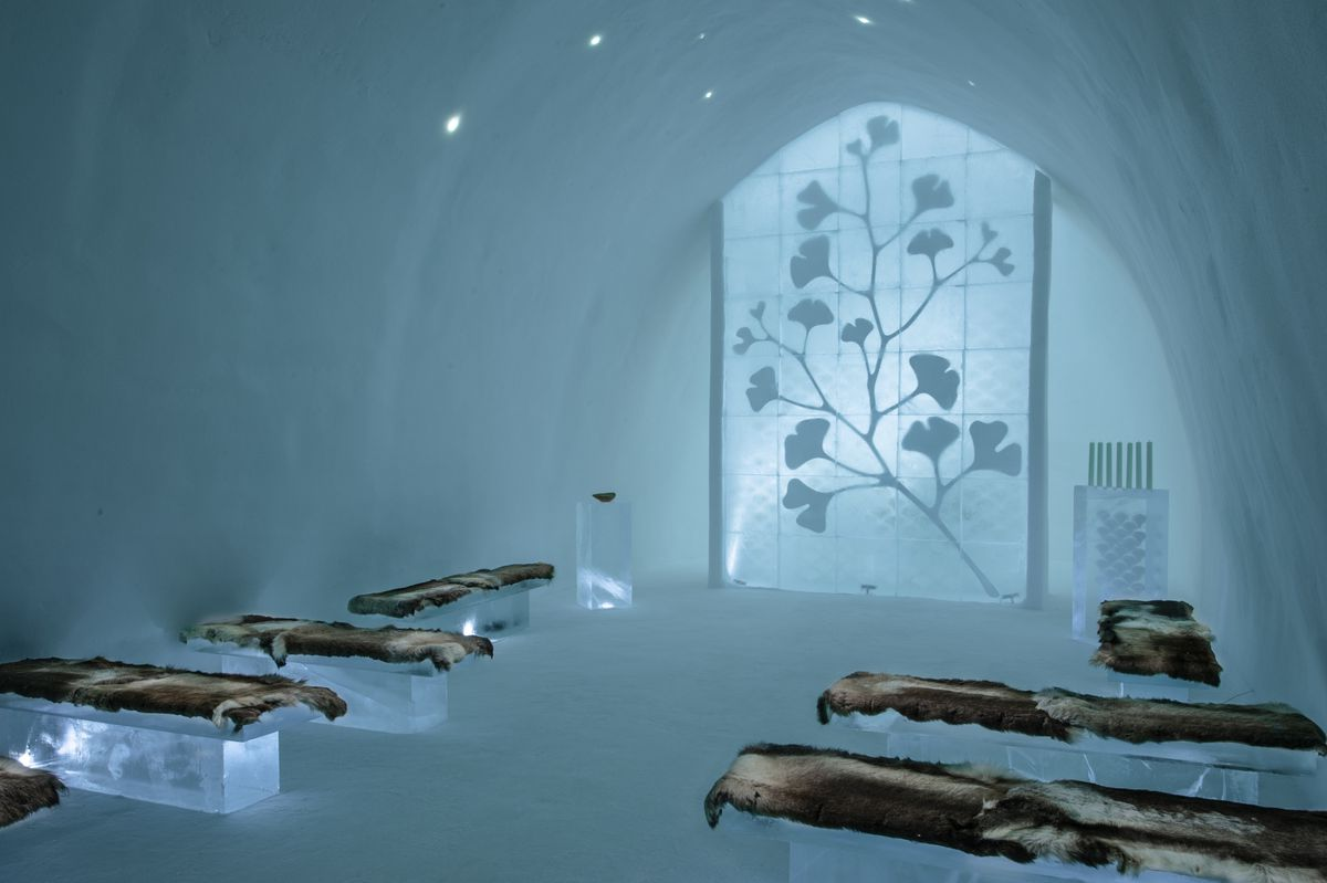 Blocks of ice provide seating in an ice cave, facing a wall depicting enlarged gingko leaves.