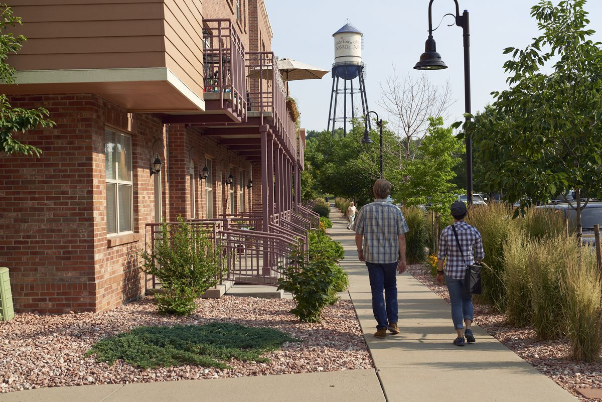 Two people strolling on a sidewalk in front of a row of newly built townhomes.
