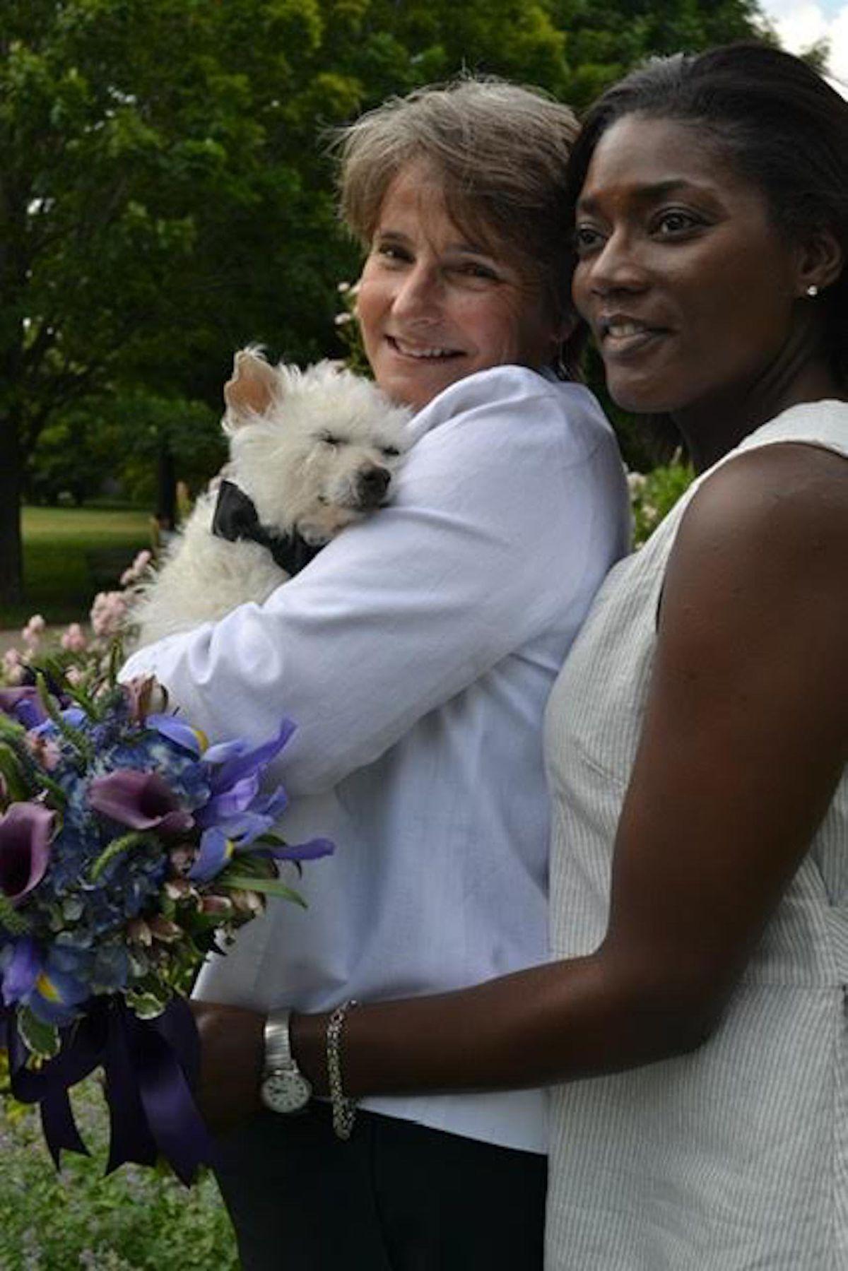 Nancy Lipman -- holding Ben, one of her rescue dogs -- with her wife Johanne M. Kenol.