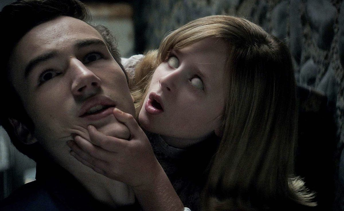 A young girl with all-white eyes and a wide-open mouth grabs a man's chin.