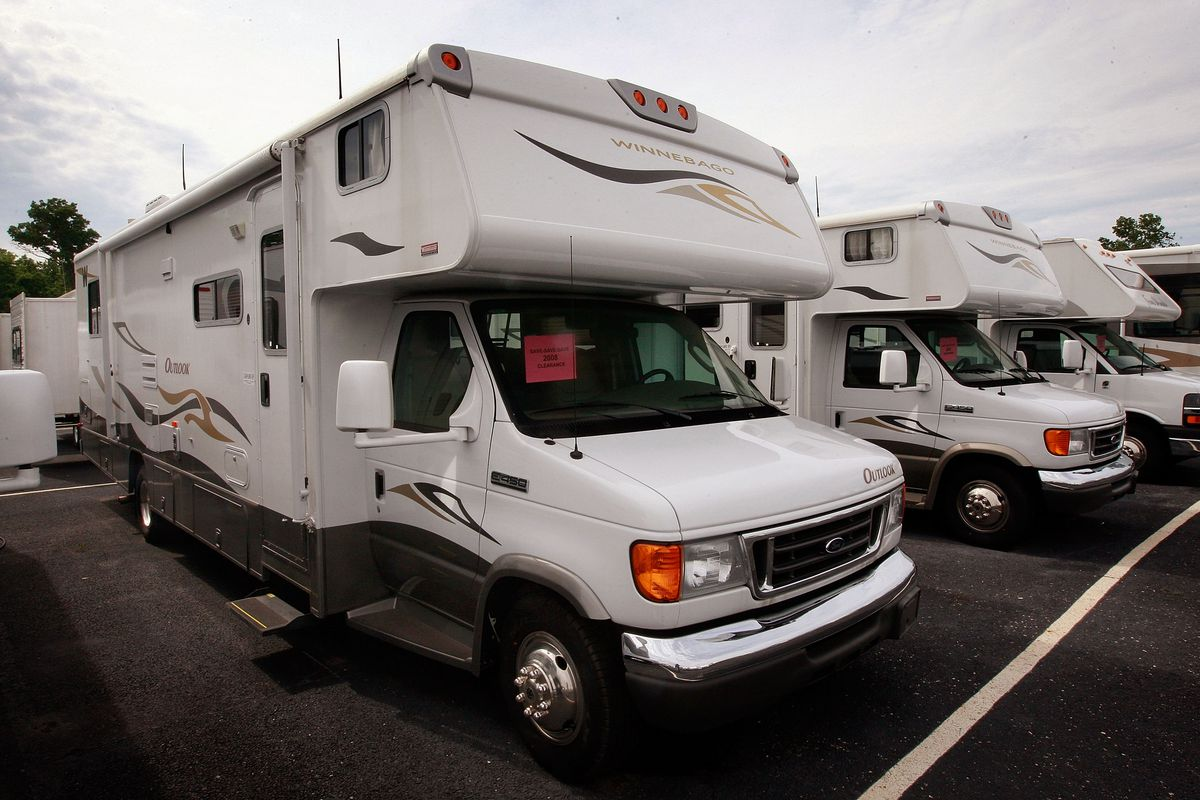 A white recreational vehicle sits on the lot of a dealership in a row of identical vehicles.