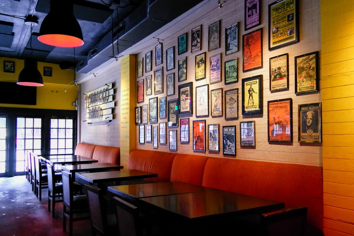 Restaurant area with red banquettes and black tables, with colorful artwork decorating the yellow wall